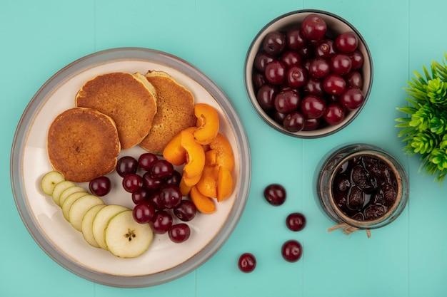 Вид сверху на блины с нарезанным абрикосом и грушей и вишней в тарелке с клубничным вареньем и вишней на синем фоне