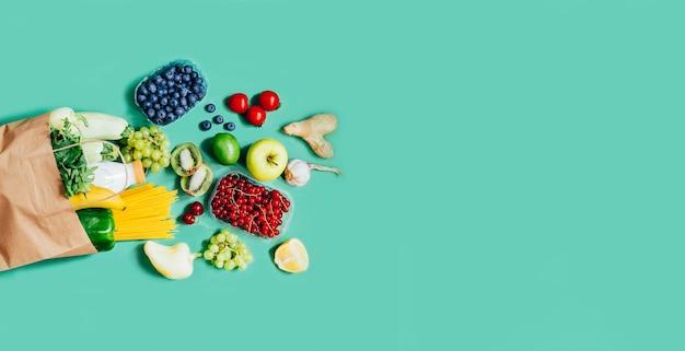 텍스트를 위한 여유 공간이 있는 녹색 배경에 식료품 야채 과일 딸기 감귤류 유제품 식료품이 든 종이 봉지의 상위 뷰