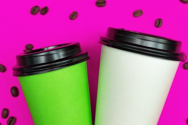 Взгляд сверху бумажных устранимых кофейных чашек на розовой поверхности с кофейными зернами.