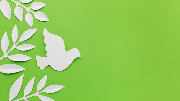 Вид сверху бумаги голубя и листьев с копией пространства