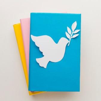 Вид сверху бумаги голубя на книгах