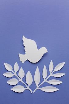 Вид сверху бумаги голубя с листьями и копией пространства