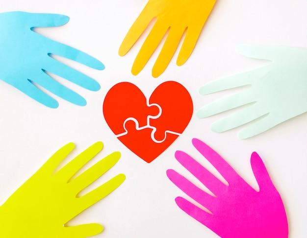 Вид сверху бумажных рук с бумажным сердцем-головоломкой