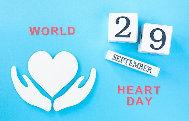 Вид сверху бумажного сердца с датой всемирного дня сердца