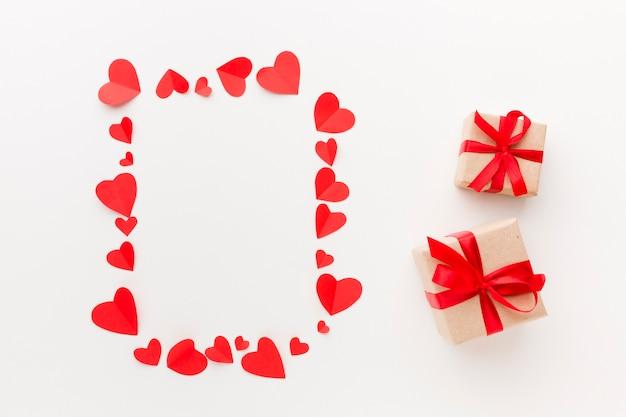 Вид сверху бумажной сердечной рамки с подарками
