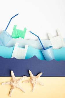 プラスチック製のカップとヒトデと紙の海の波のトップビュー
