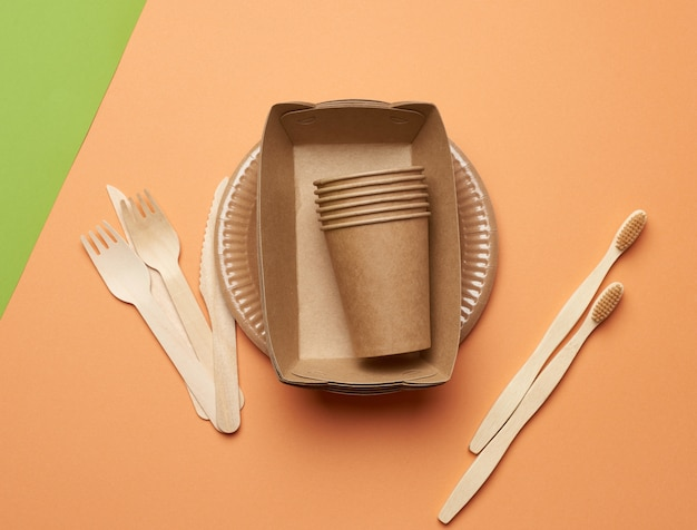 나무 포크와 나이프와 갈색 공예 종이에서 종이 접시와 컵의 상위 뷰