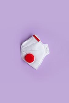 Вид сверху маски респиратора твердых частиц с красным фильтром клапана выдоха на фиолетовом фоне.
