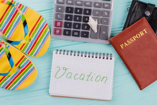 휴가 여행 계획을 의미하는 테이블 위에 있는 여권, 샌들, 계산기의 상위 뷰. 노트북에 작성 된 휴가입니다.