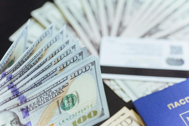 木製のデスクトップ上のドル紙幣とパスポートの上面図。