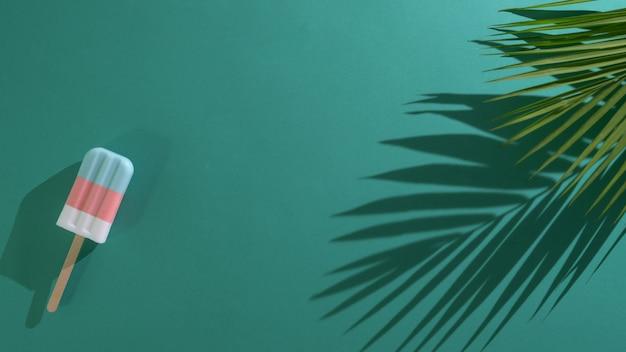 緑の背景にパステルアイスキャンディー、ヤシの葉の上から見る
