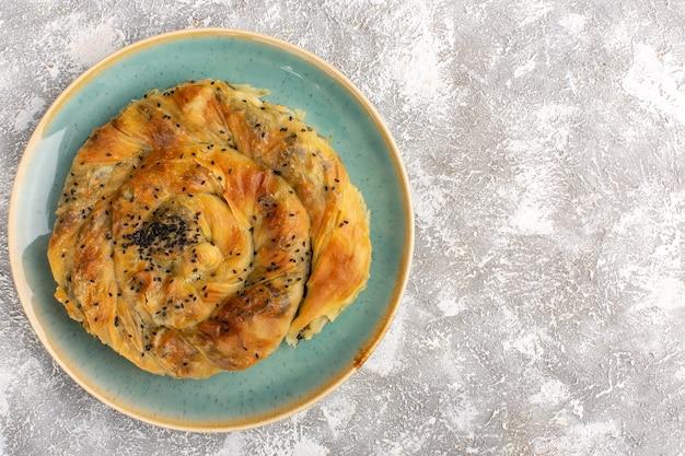 Вид сверху на тесто с мясом вкусное тесто внутри тарелки на светлой поверхности