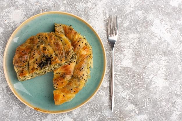 Вид сверху на тесто с мясом, вкусное тесто внутри тарелки, нарезанное на светлой поверхности