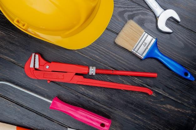 Вид сверху на узор из набора строительных инструментов в виде отвертки трубный ключ, защитный шлем, кисть и гаечный ключ на деревянном фоне