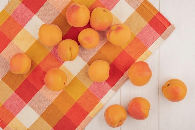 Вид сверху на узор из абрикосов на клетчатой ткани и на деревянном фоне
