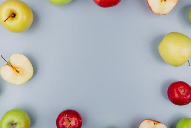 Вид сверху на узор разрезанных и целых яблок на сером фоне с копией пространства