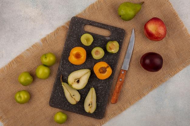 Вид сверху на узор фруктов как половину разрезанной груши абрикосовой сливы на разделочной доске и персиковой грушевой сливы с ножом на мешковине на белом фоне