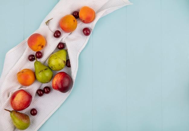コピースペースと白い布と青い背景に桃アプリコット梨チェリーとして果物のパターンのトップビュー