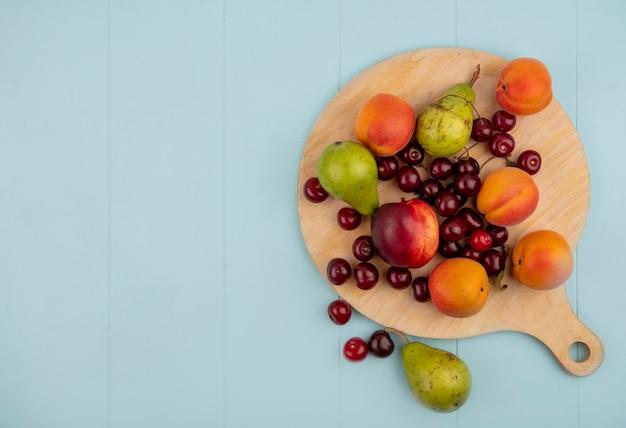 Вид сверху на узор из фруктов в виде персика, груши, абрикоса, вишни на разделочной доске и на синем фоне с копией пространства