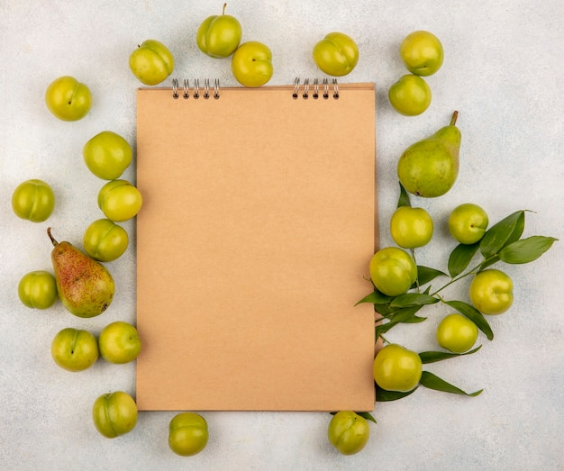 Вид сверху на узор из фруктов в виде сливы и груши с листьями вокруг блокнота на белом фоне с копией пространства