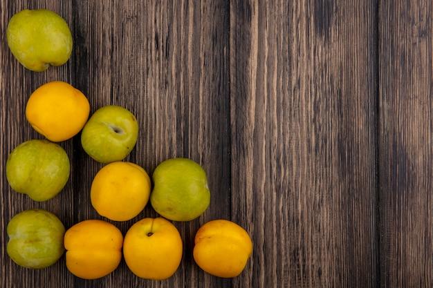 コピースペースを持つ木製の背景にプルートとネクタコットとして果物のパターンのトップビュー