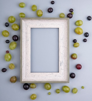 灰色の背景上のフレームの周りのブドウの果実のパターンのトップビュー
