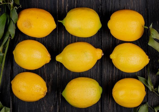 葉で飾られた木製のテーブルにレモンのパターンのトップビュー