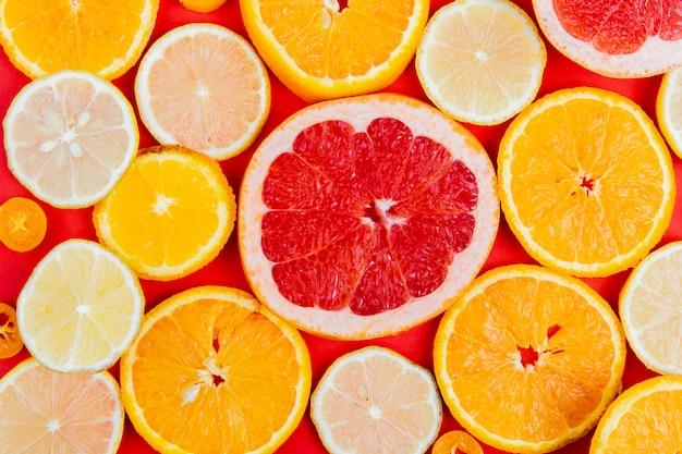 赤いテーブルにオレンジグレープフルーツレモンとしてスライスした柑橘系の果物のパターンのトップビュー