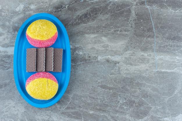 Вид сверху персикового печенья и шоколадных вафель на синей деревянной тарелке.