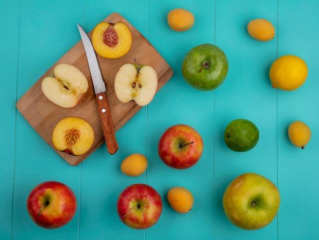 ナイフとアプリコットのボード上のリンゴの半分と桃の半分と水色の表面上のレモンとライムのトップビュー