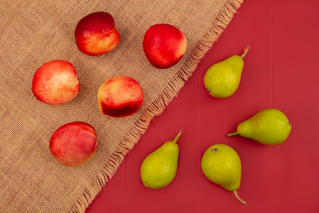 Вид сверху персика, изолированного на мешковине, и груш на красном фоне