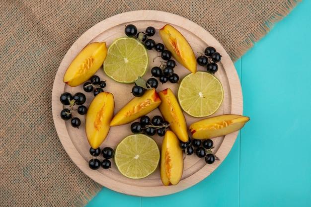 Вид сверху ломтиков персика с ломтиками черной смородины и лайма на деревянном подносе на синей поверхности