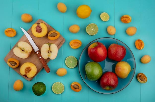 ボード上のナイフアプリコットとライムとレモンとライムの水色の表面にリンゴと桃のトップビュー
