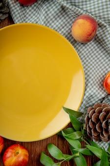 Вид сверху персики и шишка вокруг пустой тарелке на ткани на деревянной поверхности, украшенной листьями