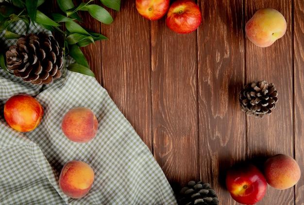 木の表面に布の上の桃と松ぼっくりのトップビュー