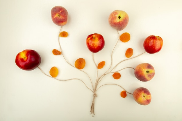 Взгляд сверху персиков и желтого изюма с шпагатом на белой поверхностной концепции дерева