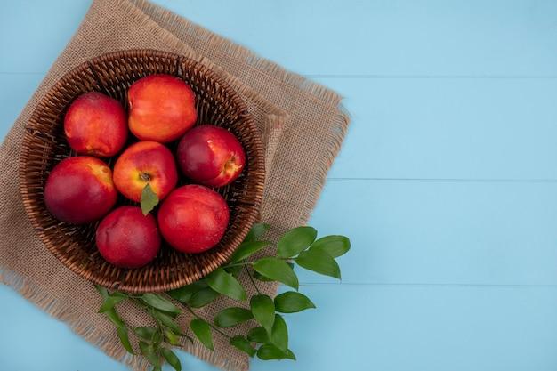 水色の表面にベージュのナプキンに葉の枝が付いているバスケットの桃のトップビュー