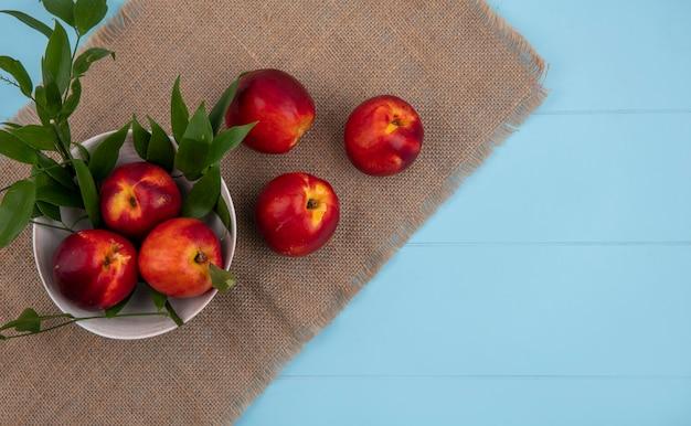 Вид сверху персиков в миске с ветвями листьев на бежевой салфетке на голубой поверхности