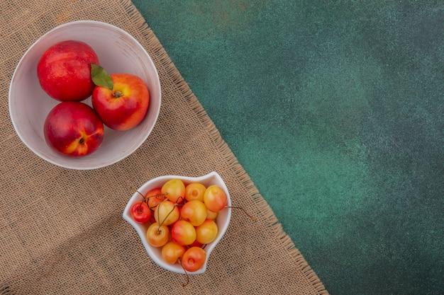 緑の表面にベージュのナプキンに白いチェリーをボウルに桃のトップビュー
