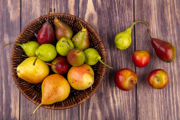 Вид сверху персиков в корзине с персиковой сливой на деревянной поверхности