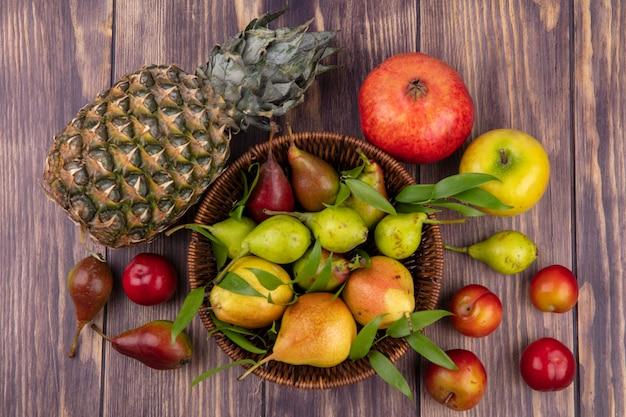 Вид сверху персиков в корзине с ананасом, яблоком, гранатом, персиком, сливой на деревянной поверхности
