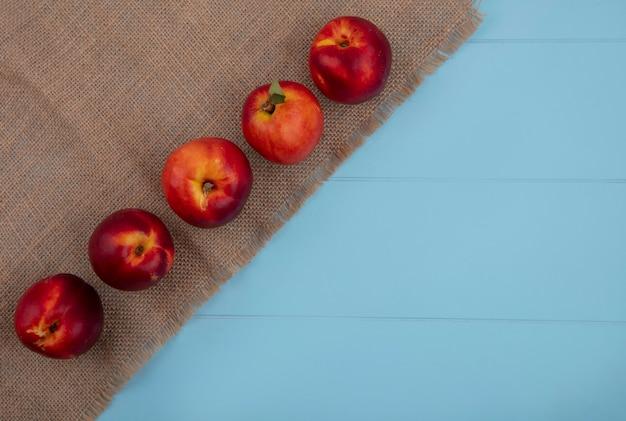 Вид сверху персиков на бежевой салфетке на голубой поверхности