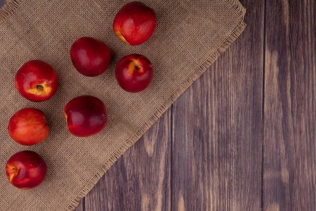 Вид сверху персиков на бежевой салфетке на деревянной поверхности