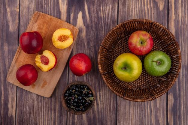 木の表面にバスケットに着色されたリンゴとボウルに黒スグリとボード上の桃のトップビュー