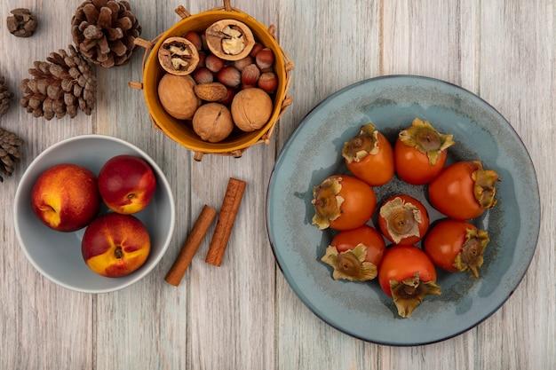 灰色の木製の表面のバケツにシナモンスティックとナッツとプレート上の柿とボウルの桃の上面図