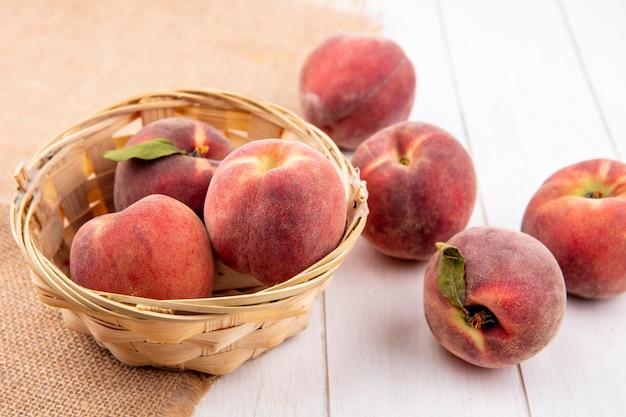 白い表面に分離された桃と袋布のバケツに桃のトップビュー