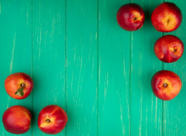 Вид сверху персиков на зеленой поверхности