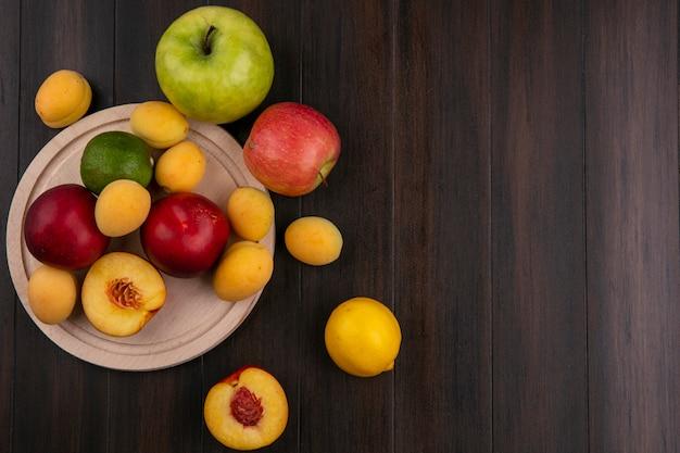 Вид сверху персиков на подставке с абрикосами и яблоками на деревянной поверхности