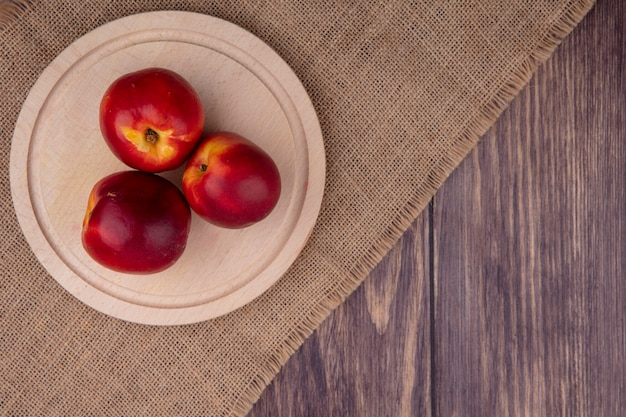 Вид сверху персиков на деревянном подносе на бежевой салфетке на деревянной поверхности