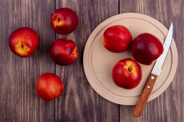木の表面にナイフで木製トレイに桃のトップビュー